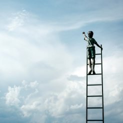 Child on a ladder reaching up into the sky