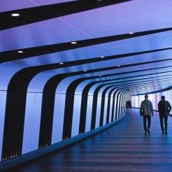 Two people walking in futuristic tunnel